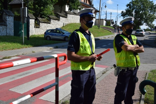 dwóch umundurowanych policjantów ruchu drogowego stojących tyłem do przejścia dla pieszych
