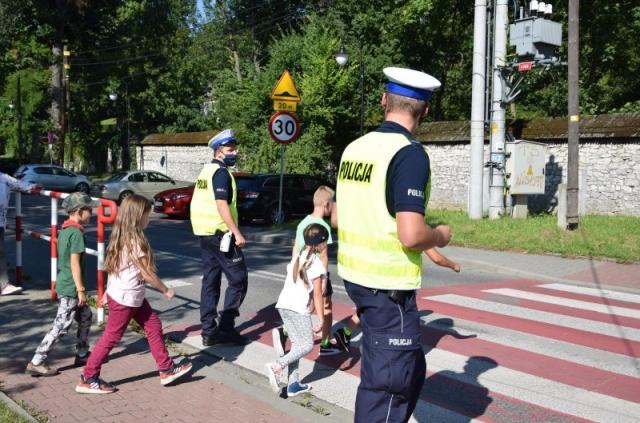 dwóch umundurowanych policjantów ruchu drogowego przeprowadzających grupę dzieci przez przejście dla pieszych