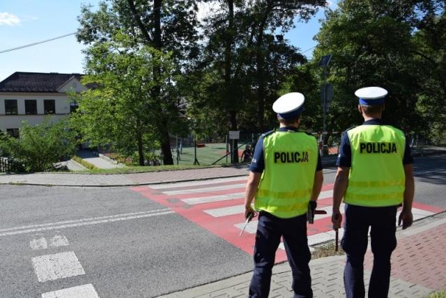 dwóch umundurowanych policjantów z ruchu drogowego stających przed przejściem dla pieszych, w tle szkoła