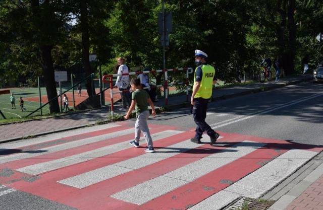 umundurowany policjant ruchu drogowego przeprowadzjący dziecko przez jezdnię