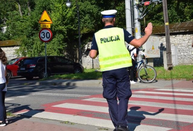 umundurowany policjant ruchu drogowego zatrzymujący pojazd przy przejściu dla pieszych