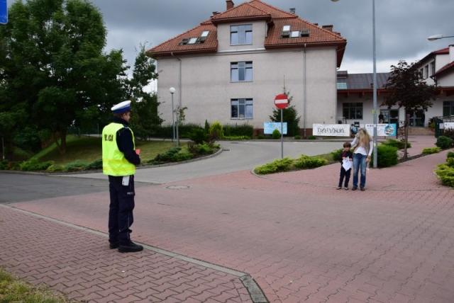 umundurowany policjant stojący przy drodze, po drugiej stronie jezdni kobieta z dzieckiem, w tle szkoła