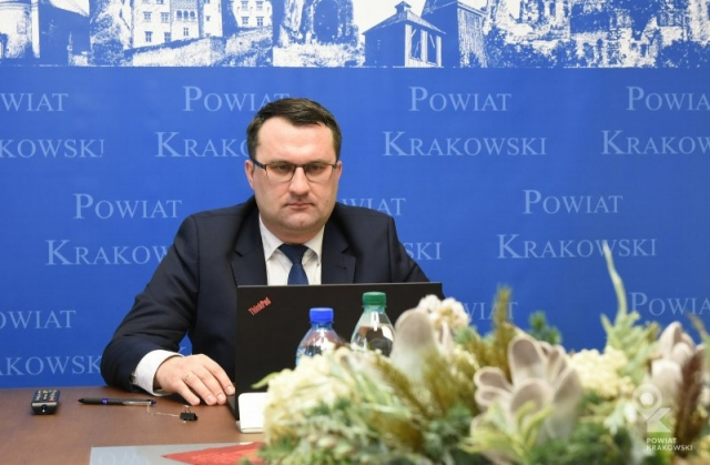 Starosta krakowski siedzi za biurkiem, przed nim otwarty laptop