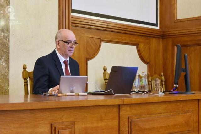 Przewodniczący Rady Powiatu w Krakowie siedzi za biurkiem, przed nim otwarty laptop
