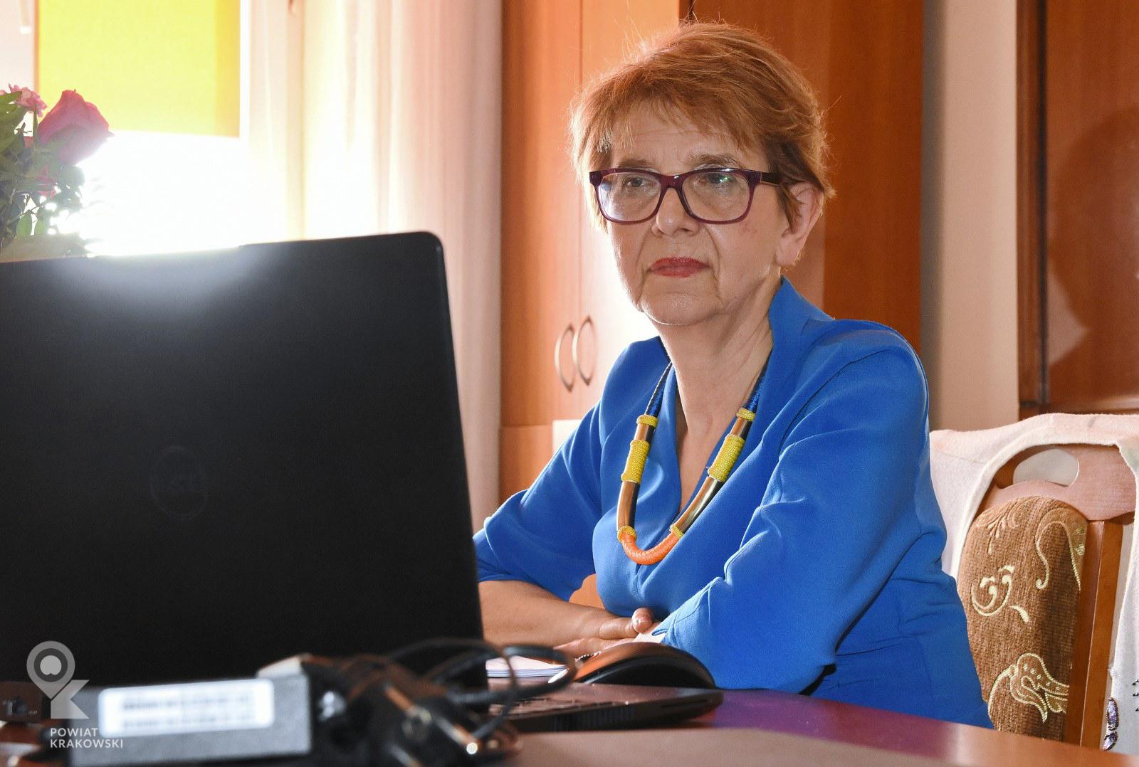 Dyrektor Wydziału Zarządzania Kryzysowego siedzi za biurkiem, przed nią otwarty laptop