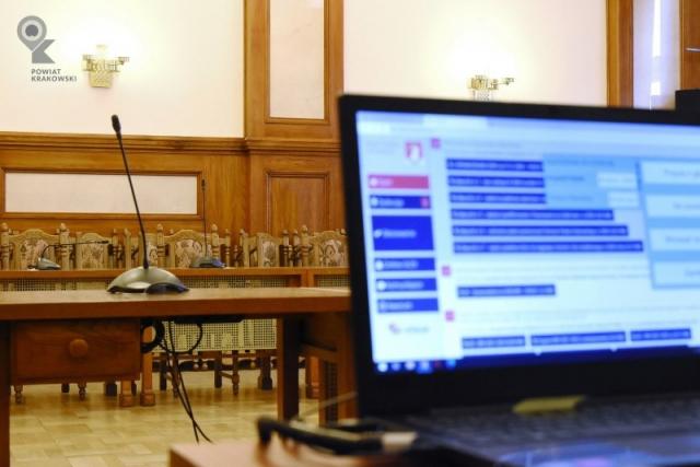 Pusta sala sesyjna, na pierwszym planie nieostry ekran laptopa z e-sesją