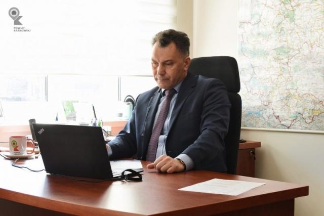 Wicestarosta siedzi za biurkiem, przed nim otwarty laptop