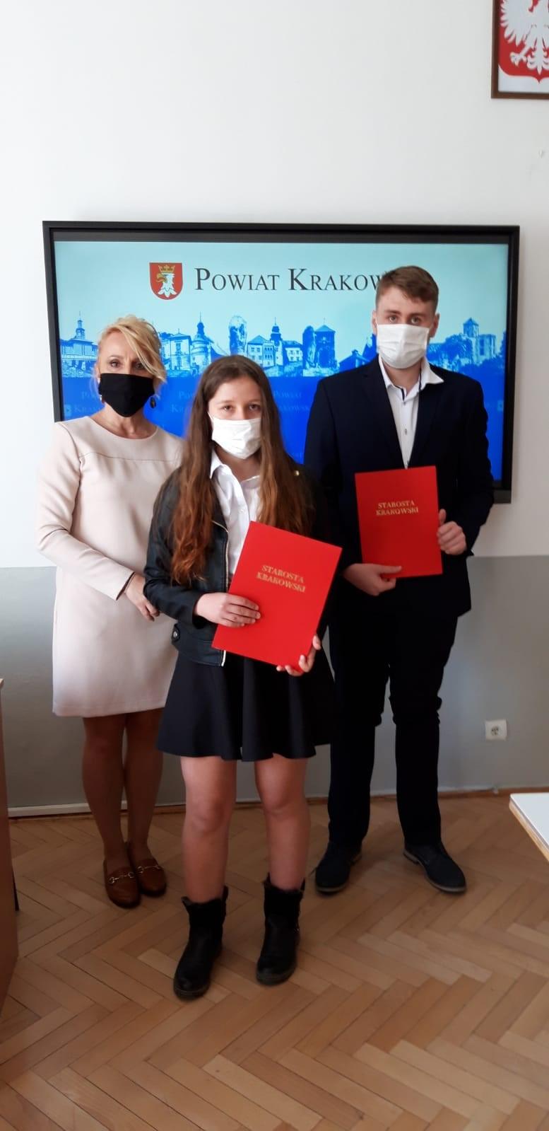 """Trzy osoby stoją przed tablicą z napisem 'POWIAT KRAKOWSKI"""". Dwie trzymają czerwone teczki z napisem """"STAROSTA KRAKOWSKI""""."""