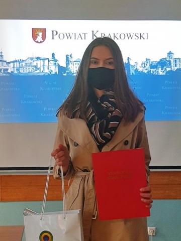 """Jedna osoba stoi przed tablicą z napisem 'POWIAT KRAKOWSKI"""", trzyma czerwoną teczkę z napisem """"STAROSTA KRAKOWSKI""""."""