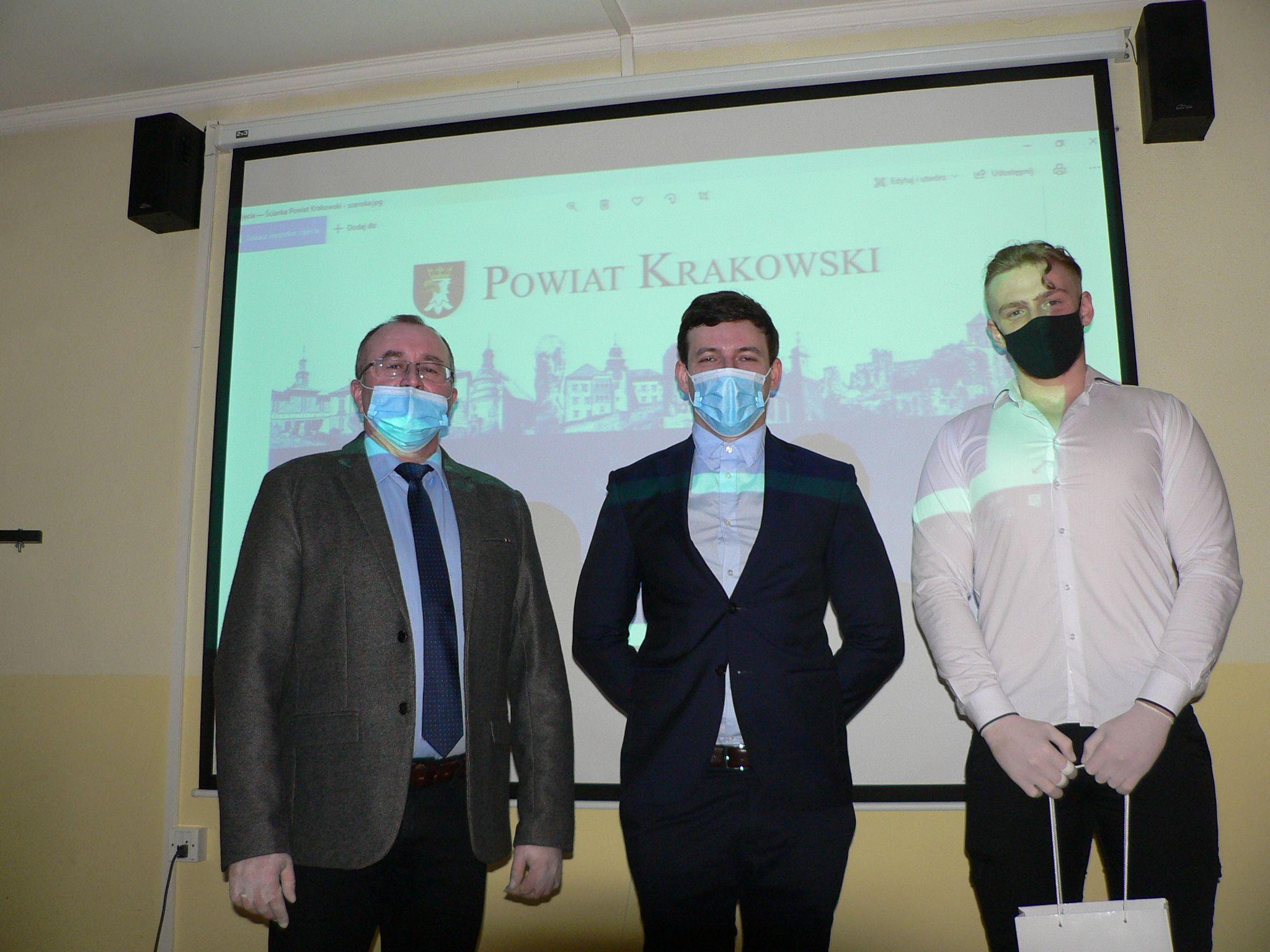 """Trzy osoby stoją przed tablicą z napisem 'POWIAT KRAKOWSKI""""."""