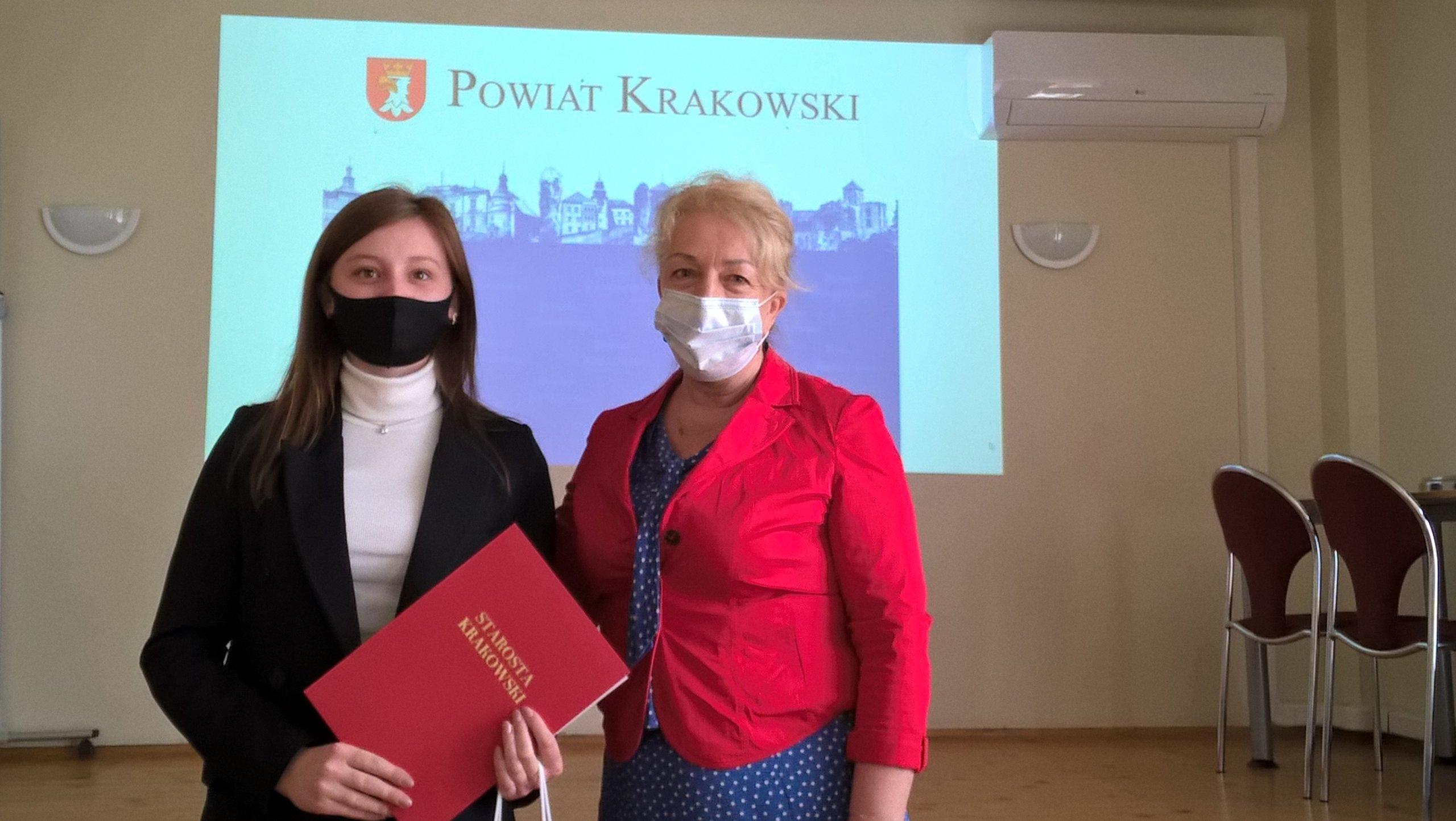 """Dwie osoby stoją przed tablicą z napisem 'POWIAT KRAKOWSKI"""". Jedna trzyma czerwoną teczką z napisem """"STAROSTA KRAKOWSKI""""."""