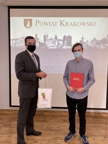 """Dwie osoby stoją przed tablicą z napisem 'POWIAT KRAKOWSKI"""". Jedna trzyma czerwoną teczkę z napisem """"STAROSTA KRAKOWSKI"""", druga białą torbę z napisem """"POWIAT KRAKOWSKI"""""""