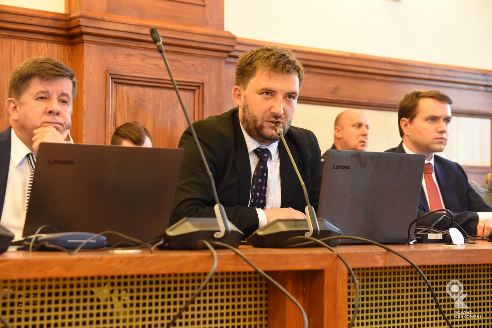 Radny Grzegorz Małodobry siedzi za stołem, mówi do mikrofonu. Przed nim otwarty laptop
