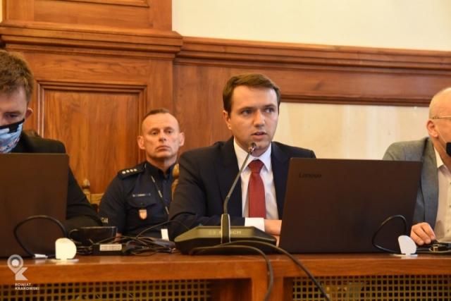 Radny Piotr Opalski siedzi za stołem,mówi do mikrofonu. Przed nim otwarty laptop