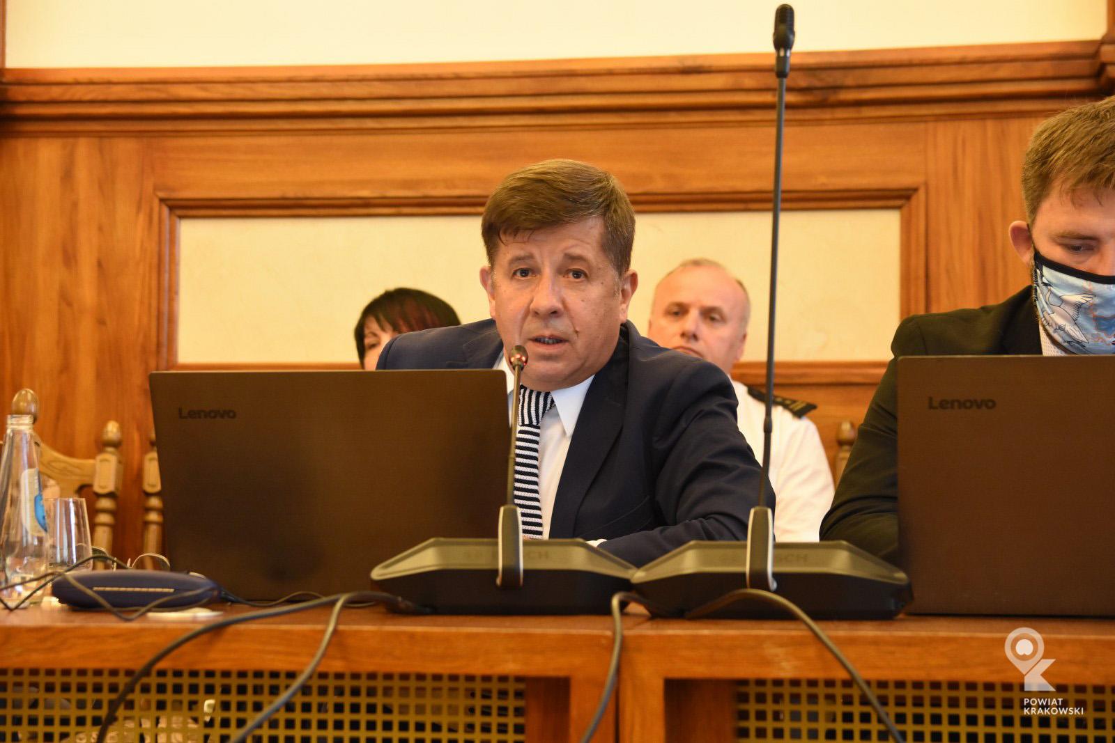 Radny Marian Janicki siedzi za stołem, patrzy w obiektyw, przemawia. Przed nim otwarty laptop