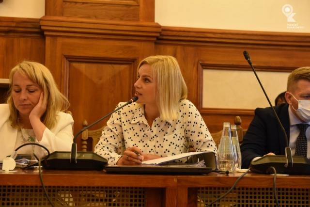 Radna Katarzyna Stadnik siedzi za stołem, patrzy w bok. Przed nią zamknięty laptop