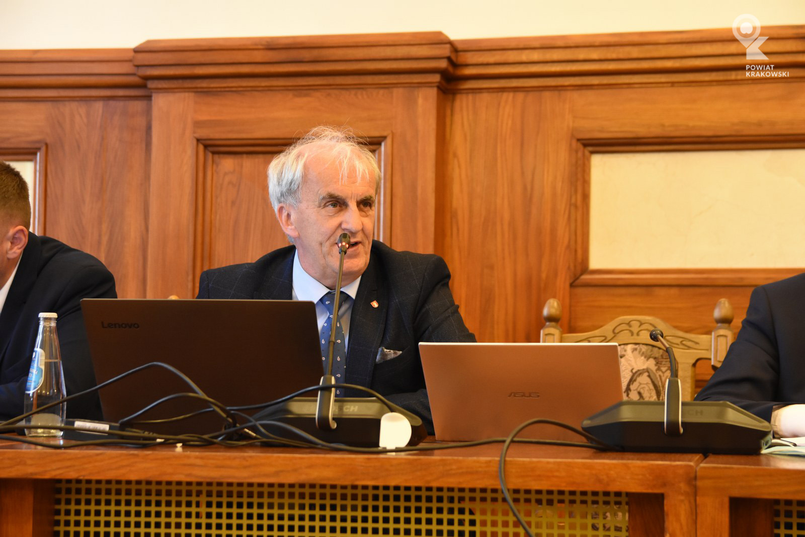 Radny Krzysztof Gębala siedzi za stołem, patrzy w bok. Przed nim otwarty laptop