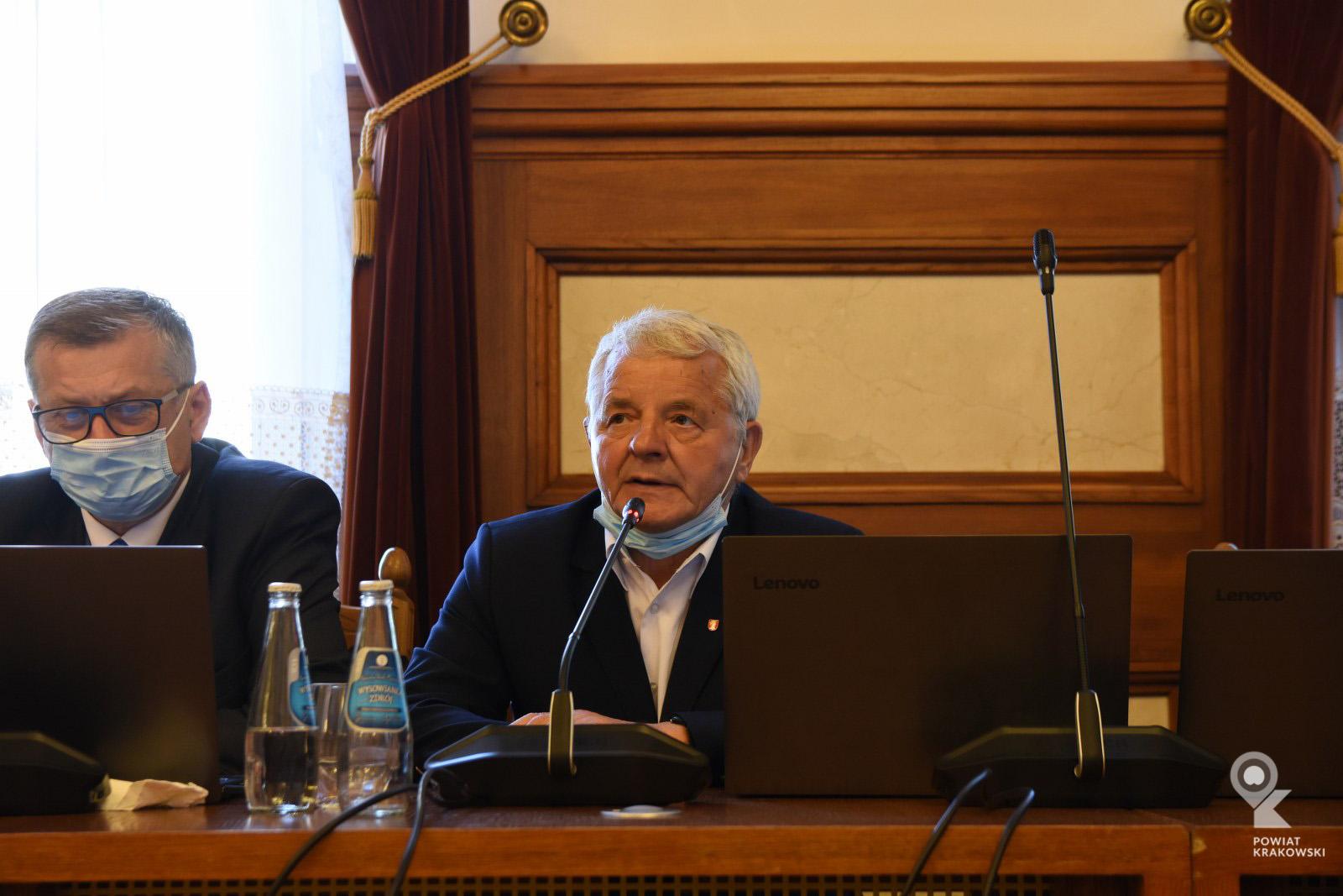Radny Leszek Dolny siedzi za stołem, mówi do mikrofonu. Przed nim otwarty laptop