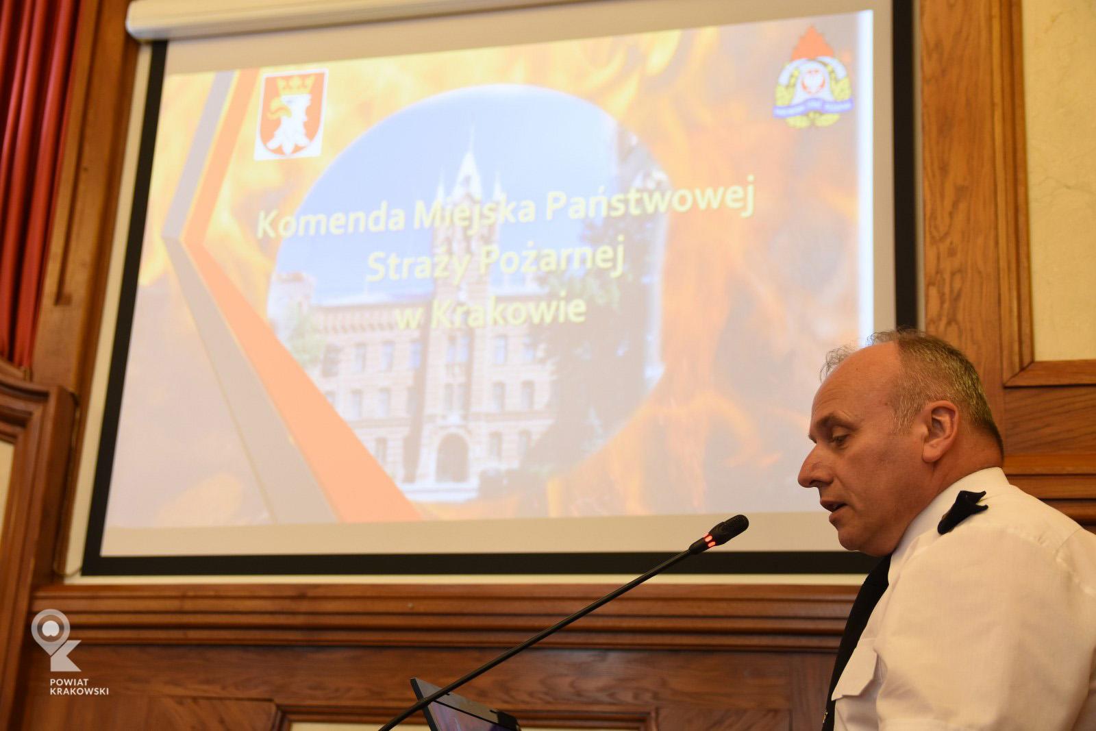 Widok ekranu prezentacyjnego, przed nim po prawej Komendant Miejski Państwowej Straży Pożarnej