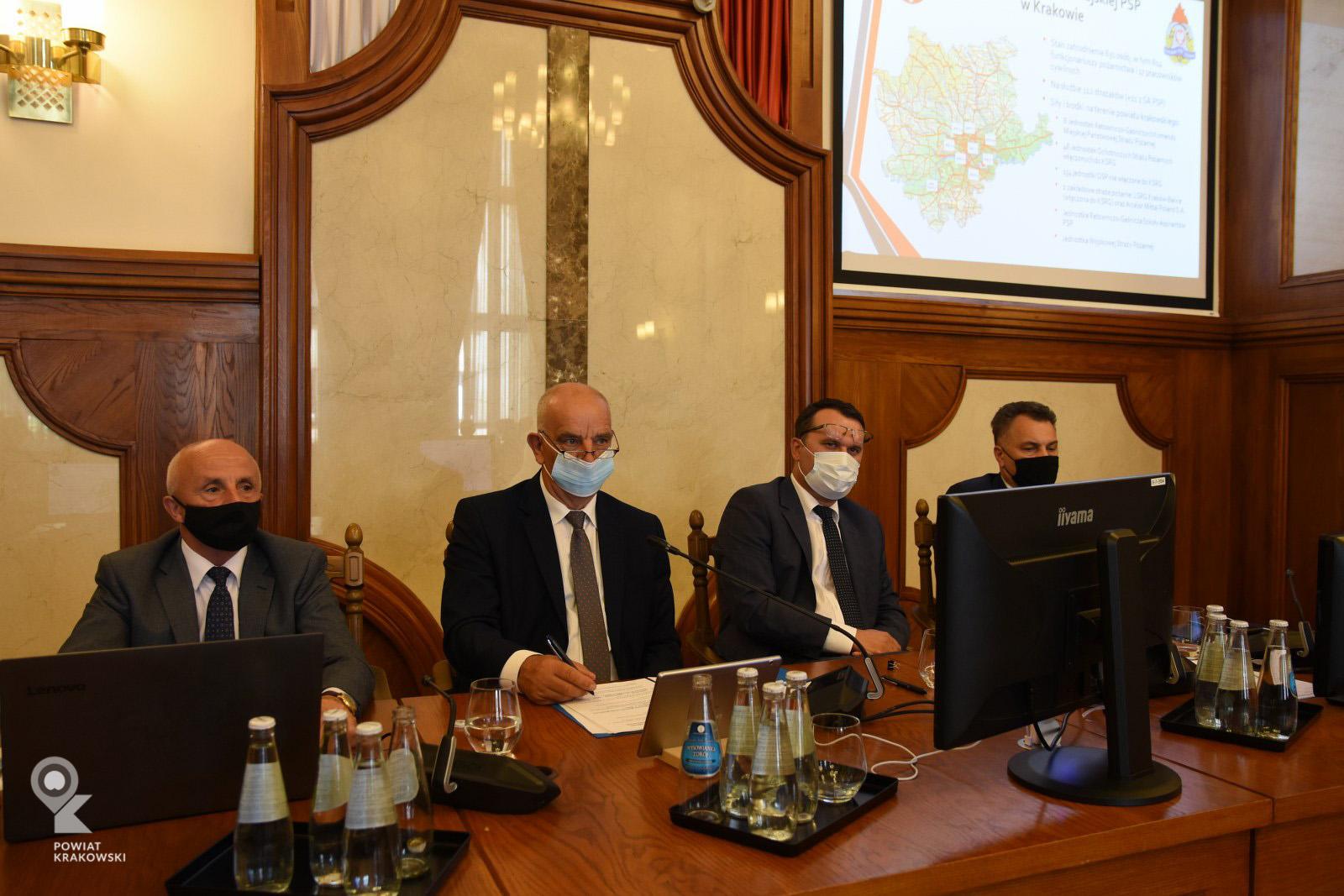Widok stołu prezydialnego, za nim siedzą od lewej: zastępca Przewodniczącego i Przewodniczący Rady Powiatu w Krakowie, Starosta Krakowski oraz Wicestarosta