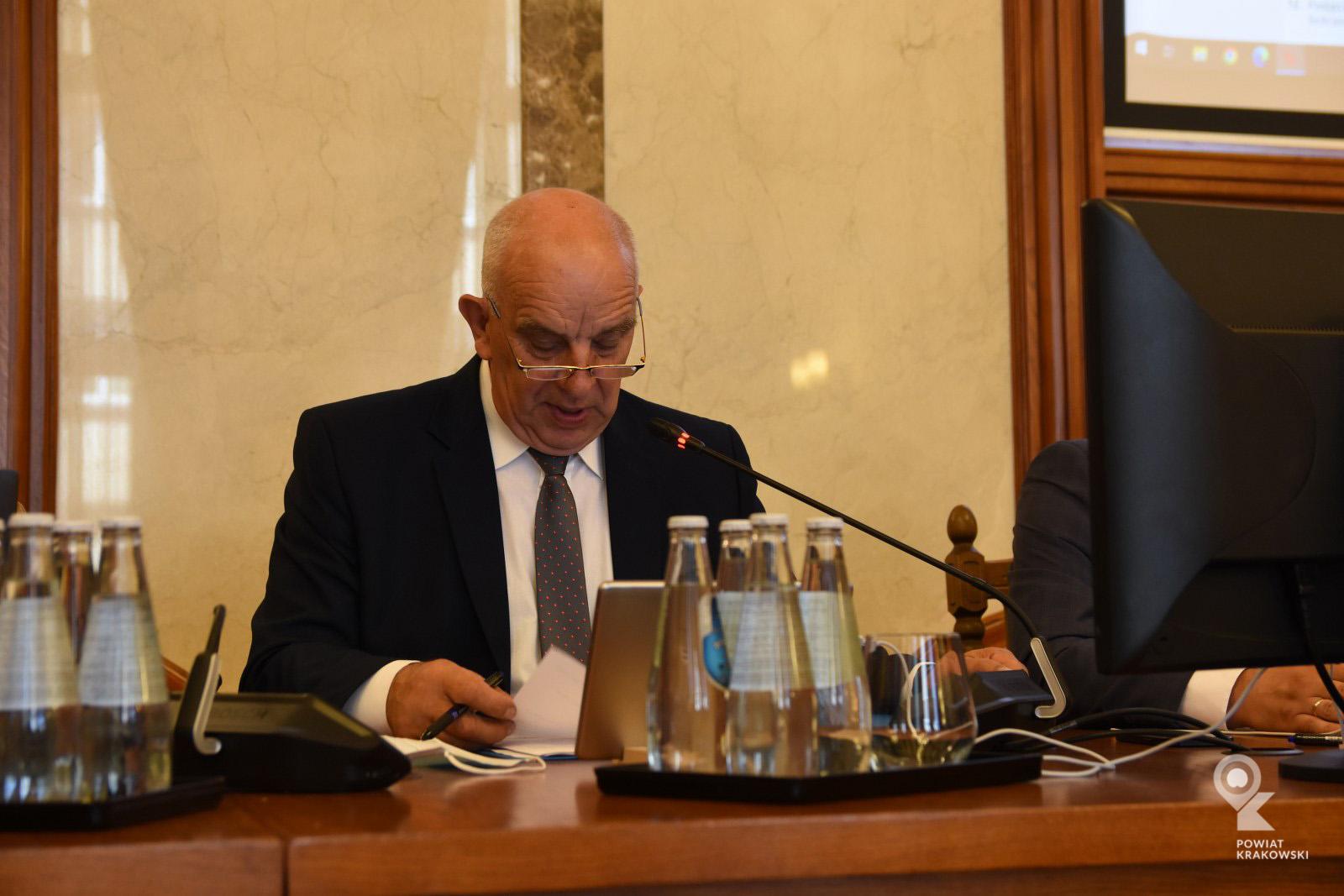 Przewodniczący Rady Powiatu w Krakowie siedzi za biurkiem, patrzy w notatki