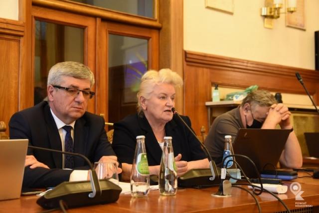 Członek Zarządu Wanda Kułaj siedzi za stołem, przemawia do mikrofonu. Przed nią otwarty laptop