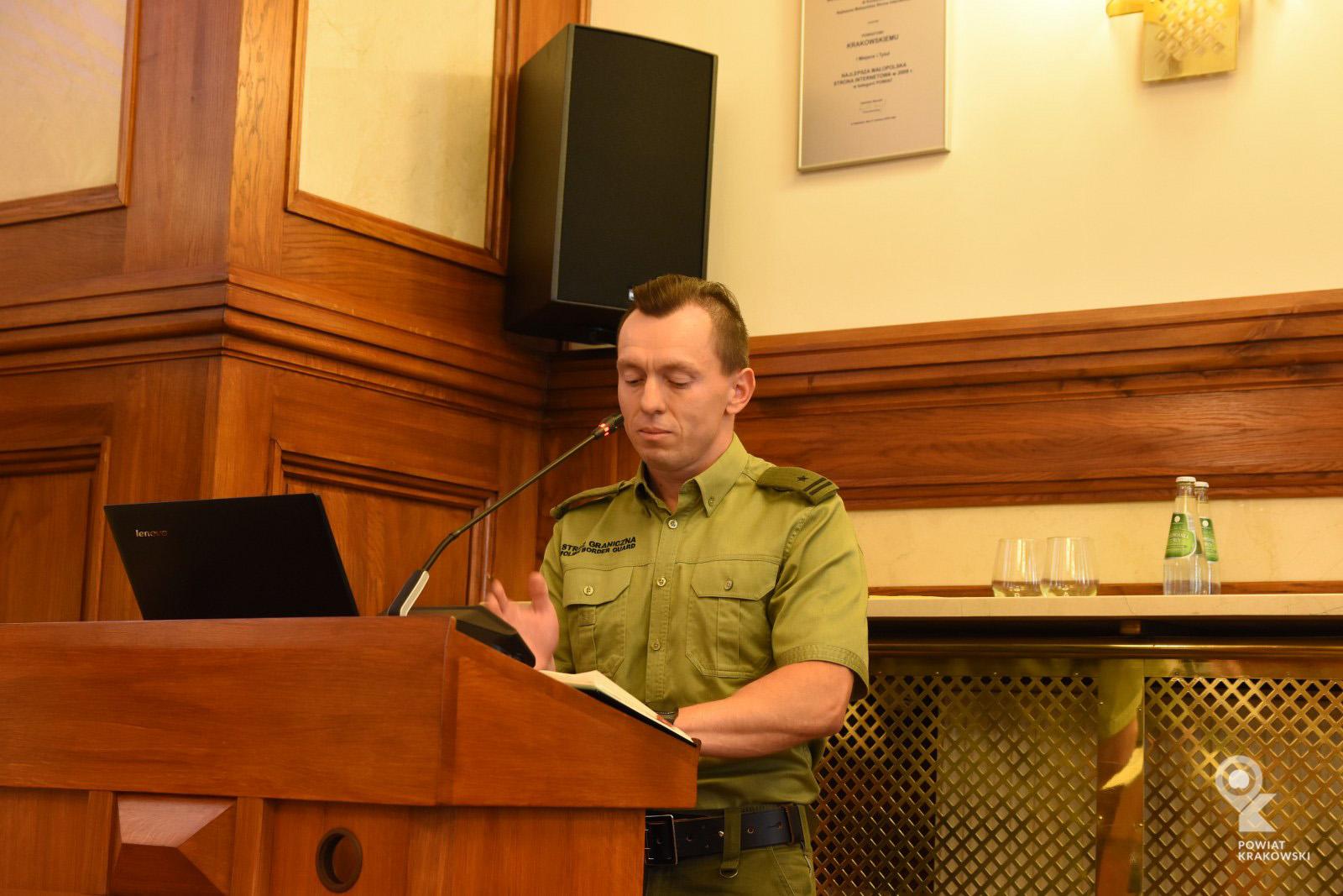 Komendant Straży Granicznej przemawia z mówicy, patrzy w notatki