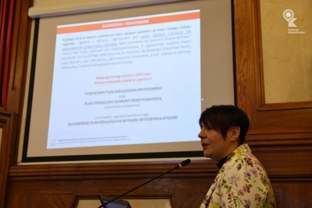 Widok ekranu prezentacyjnego, przed nim po prawej dyrektor Wydziału dyrektor Wydziału Bezpieczeństwa i Zarządzania Kryzysowego Starostwa Powiatowego w Krakowie
