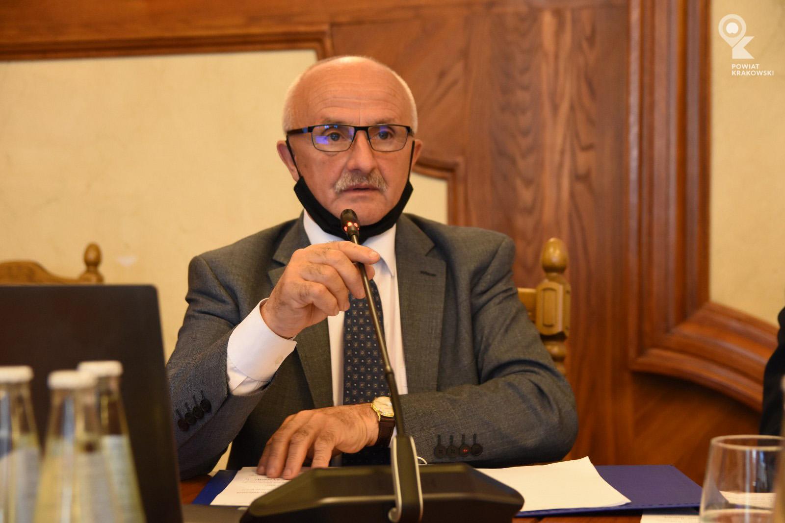 Wiceprzewodniczący Rady Powiatu siedzi za biurkiem, mówi do mikrofonu