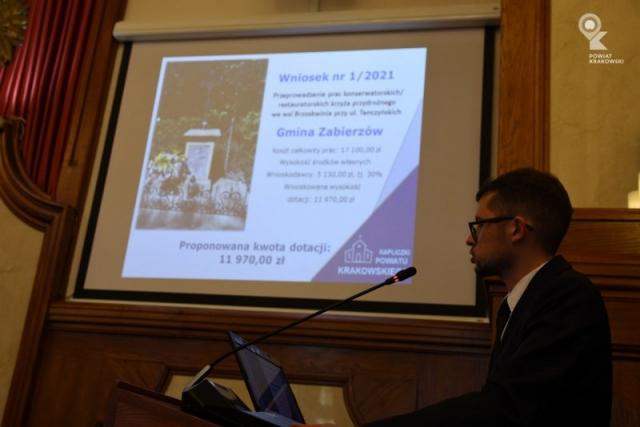 Widok ekranu prezentacyjnego, przed nim po prawej kierownik Biura ds. Strategii i Rozwoju