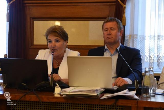Radna Janina Grela siedzi za stołem, mówi do mikrofonu. Przed nią otwarty laptop