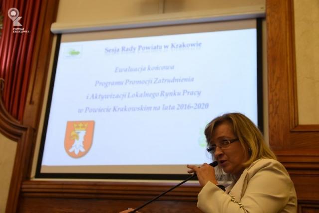 Widok ekranu prezentacyjnego, przed nim po prawej dyrektor Urzedu Pracy Powiatu Krakowskiego