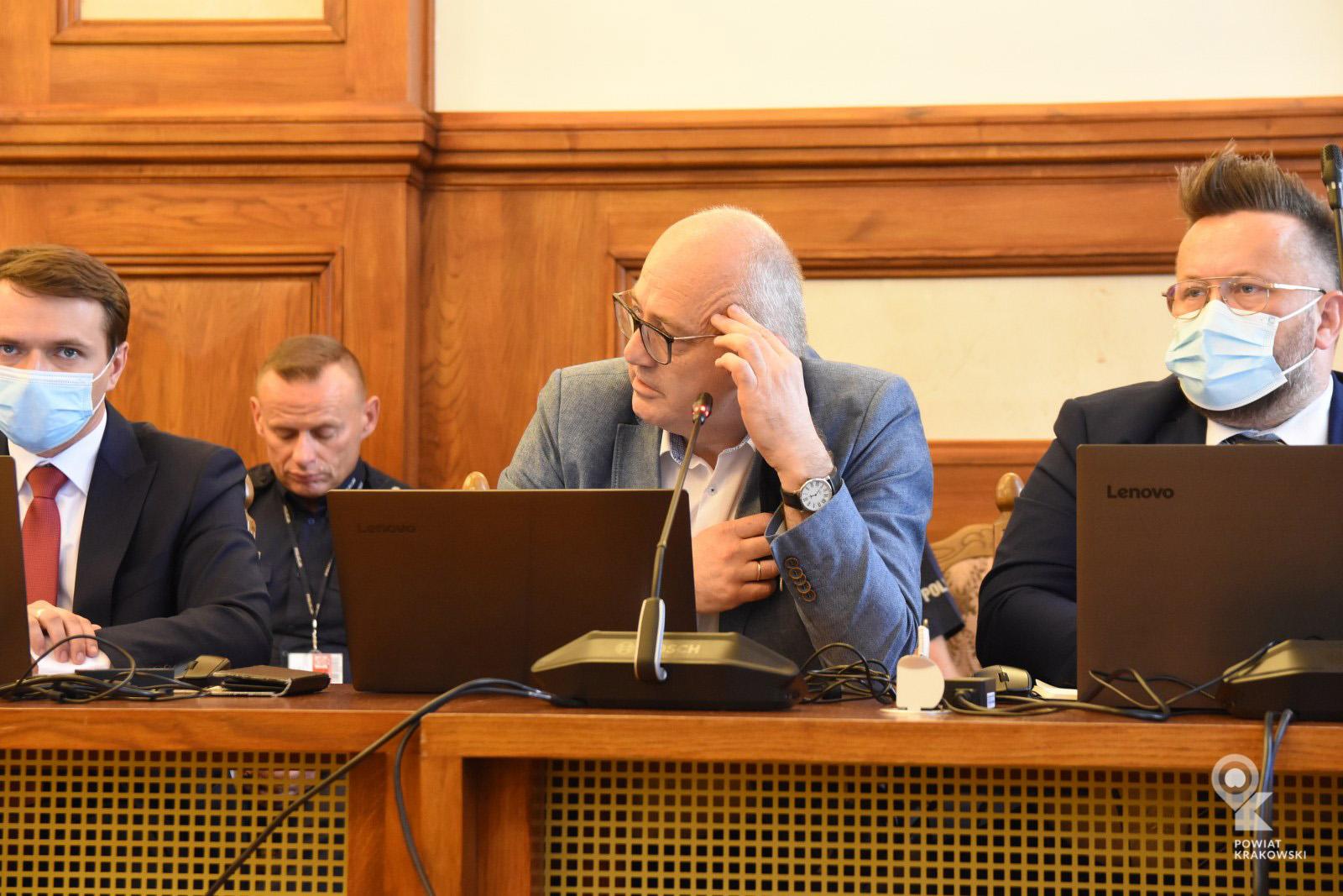 Radny Krzysztof Bosak siedzi za stołem, patrzy w bok. Przed nim otwarty laptop