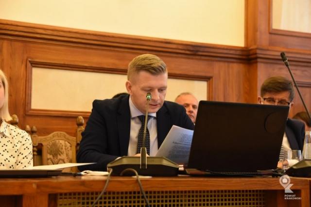 Radny Łukasz Krupa siedzi za stołem, patrzy w notatki. Przed nim otwarty laptop