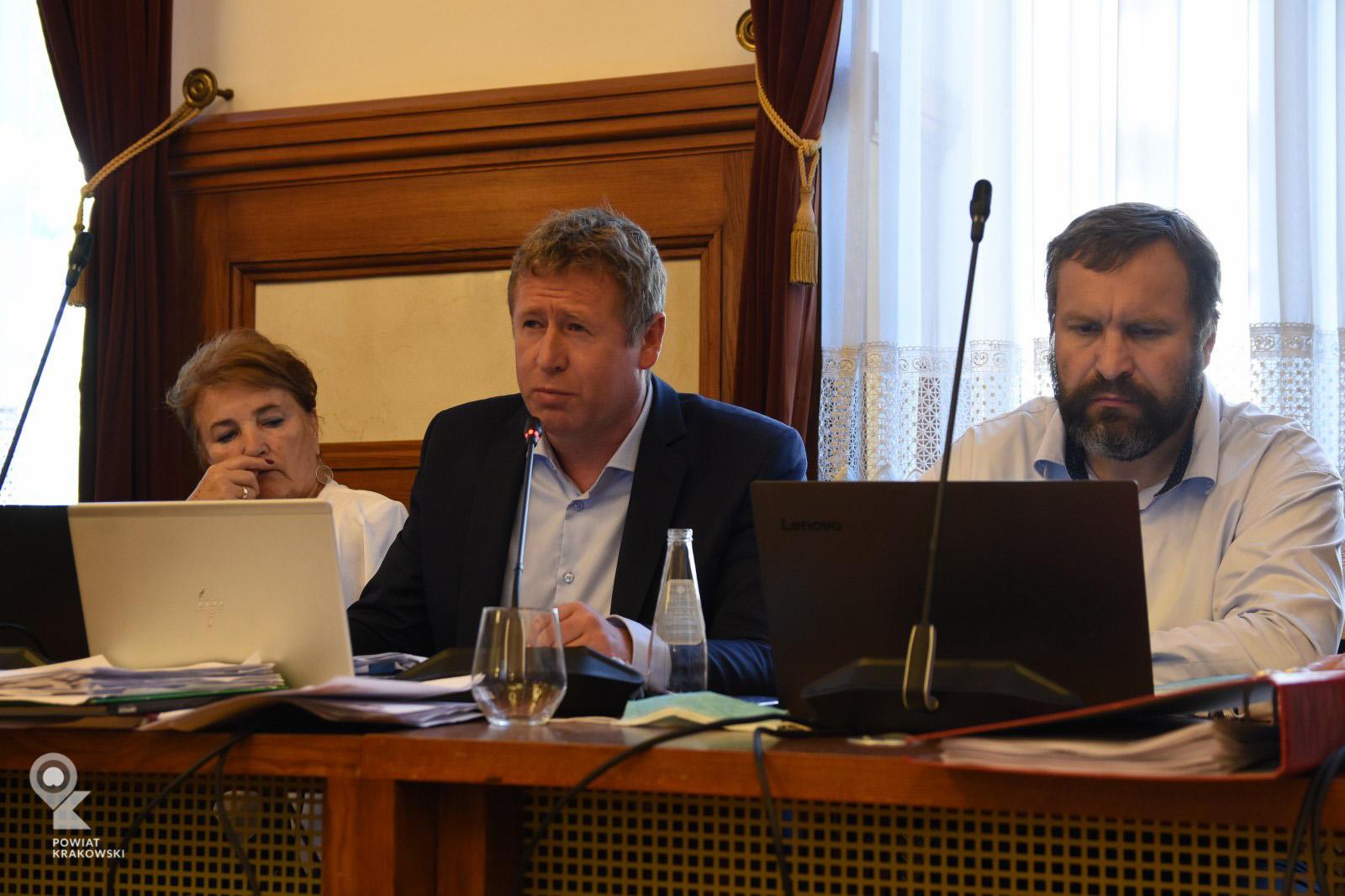 Radny Jarosław Raźny siedzi za stołem, patrzy w przód. Przed nim otwarty laptop