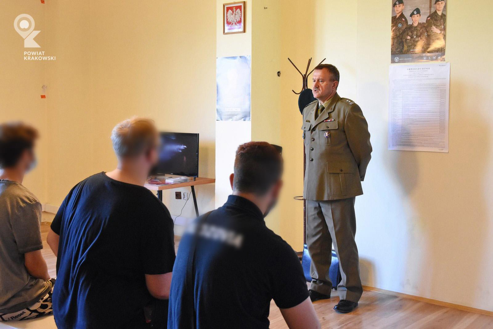 Wojskowy Komendant Uzupełnień ppłk mgr inż. Piotr Waręcki mówi do grupy siedzących chłopaków