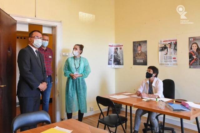 Starosta Krakowski Wojciech Pałka ogląda pokój, towarzyszą mu kobieta i mężczyzna, druga kobieta siedzi przy biurku