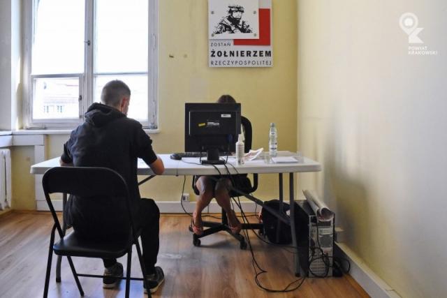"""Pokój z plakatem """"Zostań żołnierzem Rzeczypospolitej"""", biurko, przed biurkiem młody chłopak siedzi tyłem, za biurkiem i monitorem komputera kobieta"""