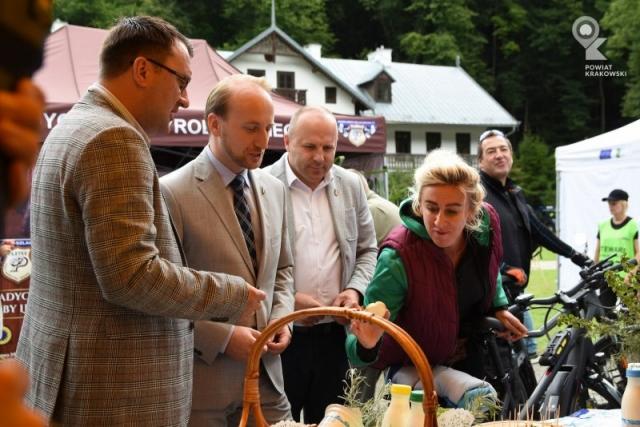 Kobieta i trzech mężczyzn rozmawiają przy stoisku degustacyjnym