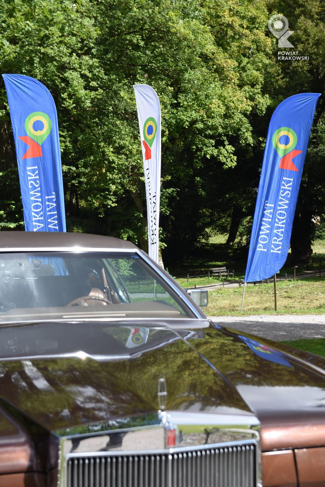 Fragment zabytkowego samochodu na pierwszym planie, na drugim flagi powiatu krakowskiego