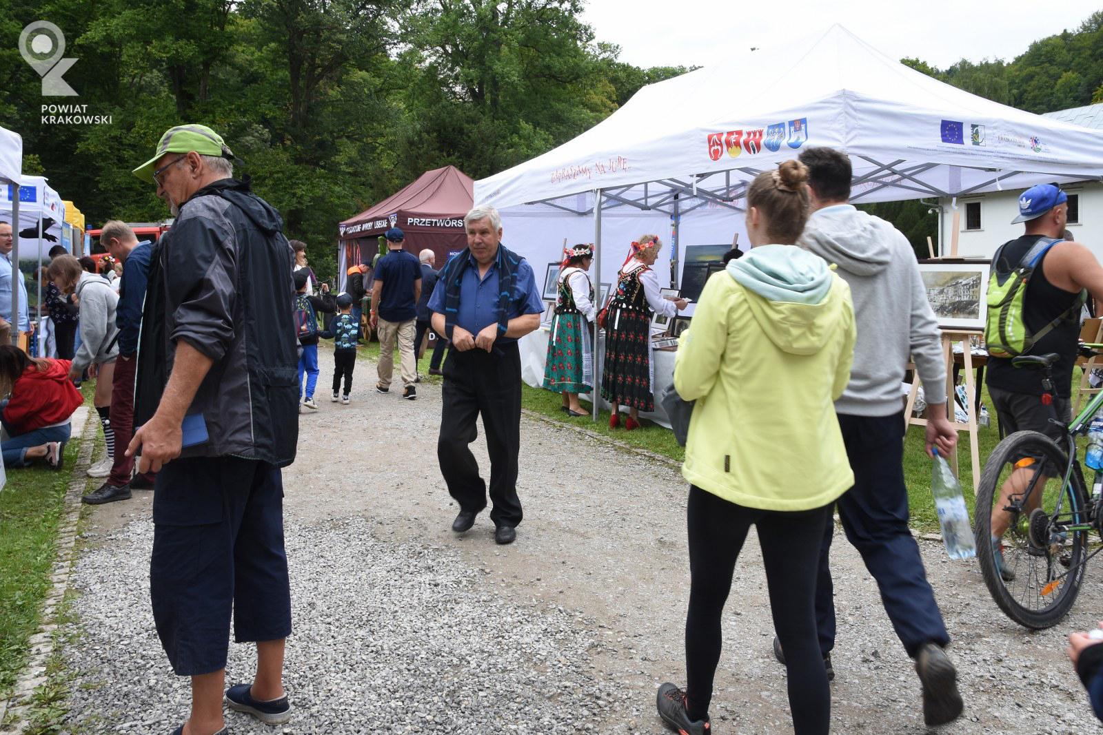 Widok ogólny pikniku - grupy osób i namioty wystawowe