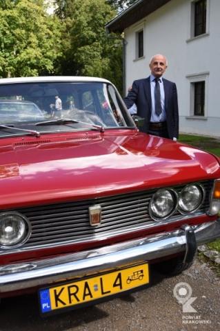 Mężczyzna przy zabytkowym czerwonym fiacie 125p