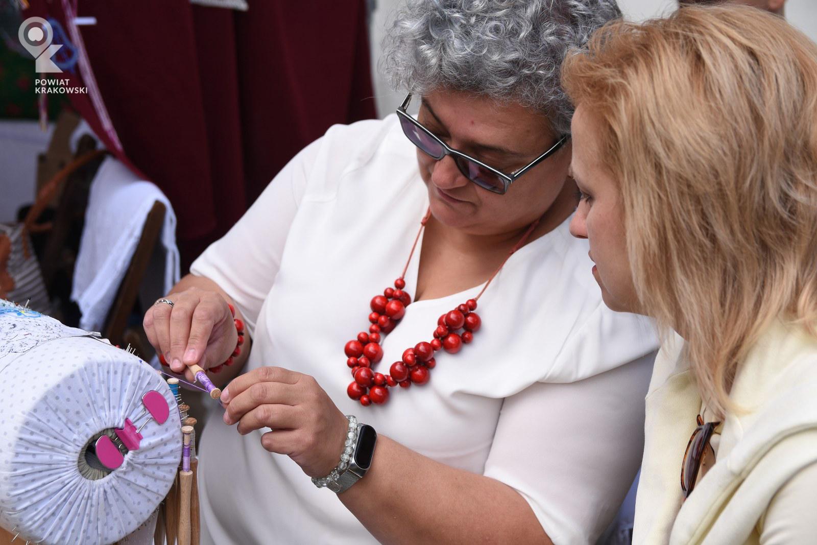 Kobieta pokazuje drugiej kobiecie, jak tworzy koronkę