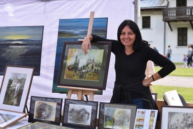 Uśmiechnięta kobieta opiera ramię na obrazie przedstawiającym Rynek w Krakowie. Przed nią i za nią obrazy