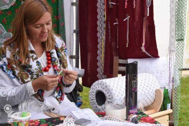Kobieta w stroju ludowym tworzy koronkę