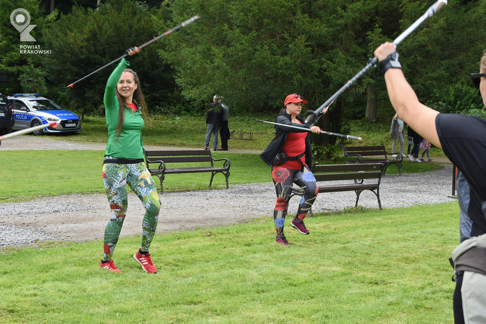Grupa kobiet ćwiczy na łące z kijami do nordic walkingu