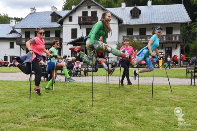 Grupa kobiet na łące, podskakują wspierając się na kijach do nordic walkingu