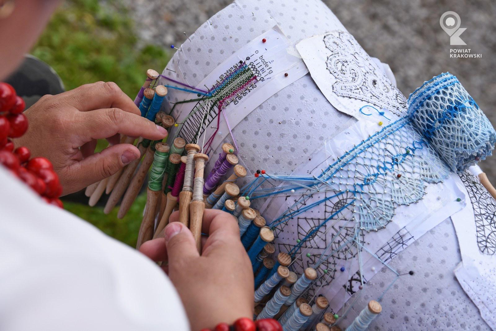 Walec z paskami ze wzorem, wbitymi szpilkami i koronkami w trakcie powstawania