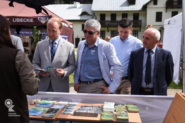 Czterech mężczyzn stoi przed stoiskiem, przeglądają materiały i słuchają osoby stojącej tyłem do obiektywu