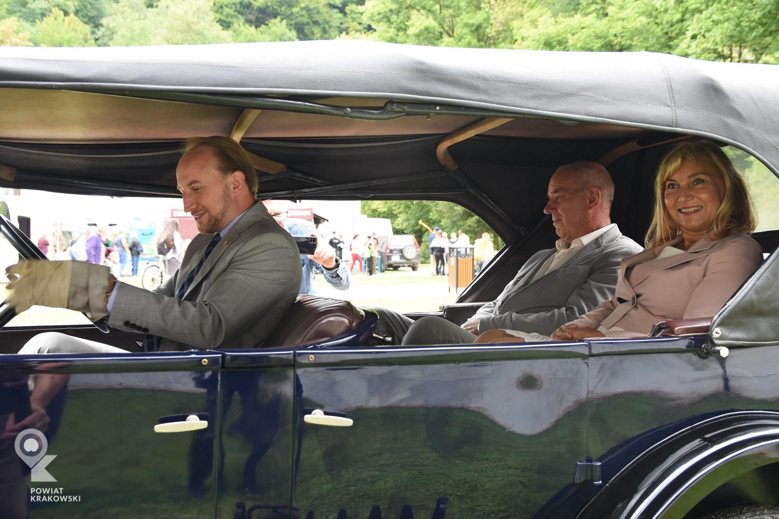 Kobieta i mężczyzna siedzą z tyłu zabytkowego samochodu, z przodu mężczyzna w rękawicach za kierownicą